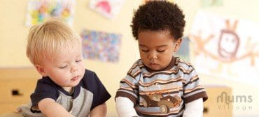 caucasian and black baby boys playing together