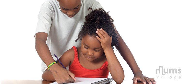 Boy helping girl write