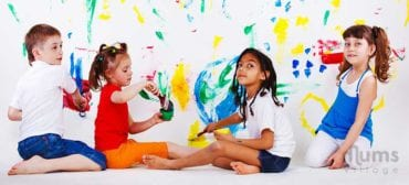 creative children painting on white wall