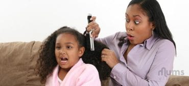 Mother combing girls long hair