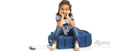 cute girl sitting on suitcase