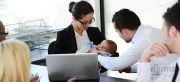 woman feeding baby with colleagues watching