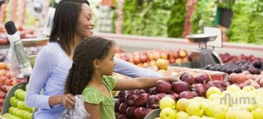 happy mother and daughter shopping for fruits