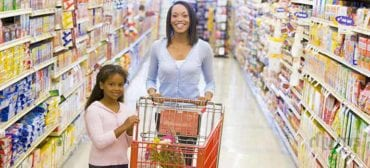 mother-and-daughter-in-supermarket-with-shopping-cart