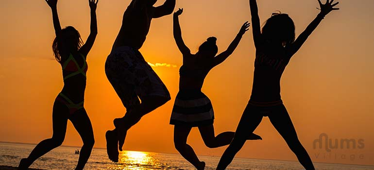 group of people jumping at the beach