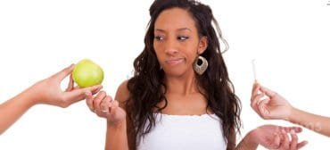 black woman making a choice between apple and cigarette